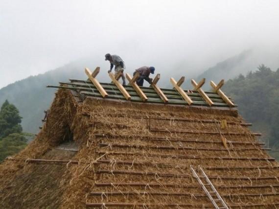 茅葺き工事 ・ 屋根の頂部で棟木の形を整えているところ