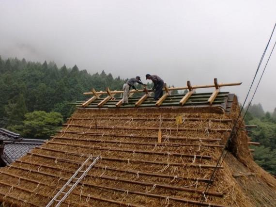 茅葺き工事 ・ 棟木と茅葺き職人さん (棟木の形を整えているところ)