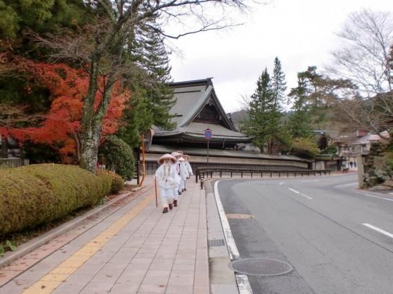 高野山内の道路脇に設置された「木製ガードレール」 (白装束の信者さんと調和したベストショット)