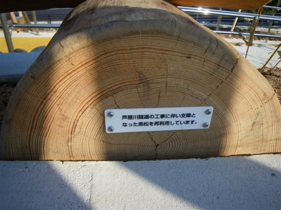 園名板の足部分に貼りつけられた松材の由来プレート