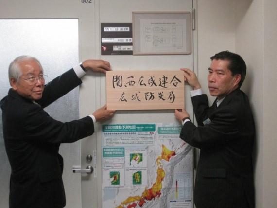 「関西広域連合地域防災局」の看板を掲げる井戸知事と木村防災監