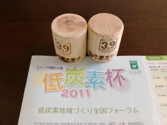 「 『低炭素杯2011』のパンフレット 」 と 弊社提供の「間伐材グッズ」