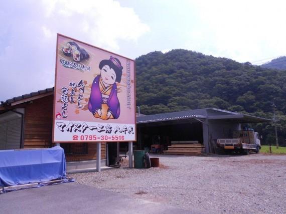 「マイスター工房八千代」の大きな看板  (同業者の木材置き場がだんだん小さくなってしまった……)