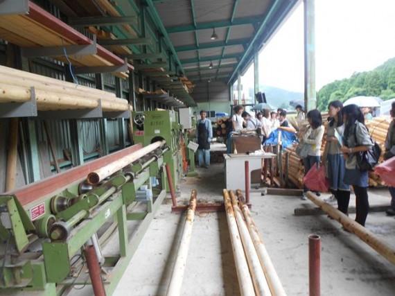 「丸棒加工機」での間伐材の加工風景を見学する大学生