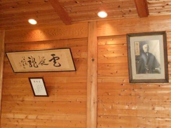 「静岡県森林組合連合会・天竜共販所」の講堂に掛かる「金原明善翁」の写真と書